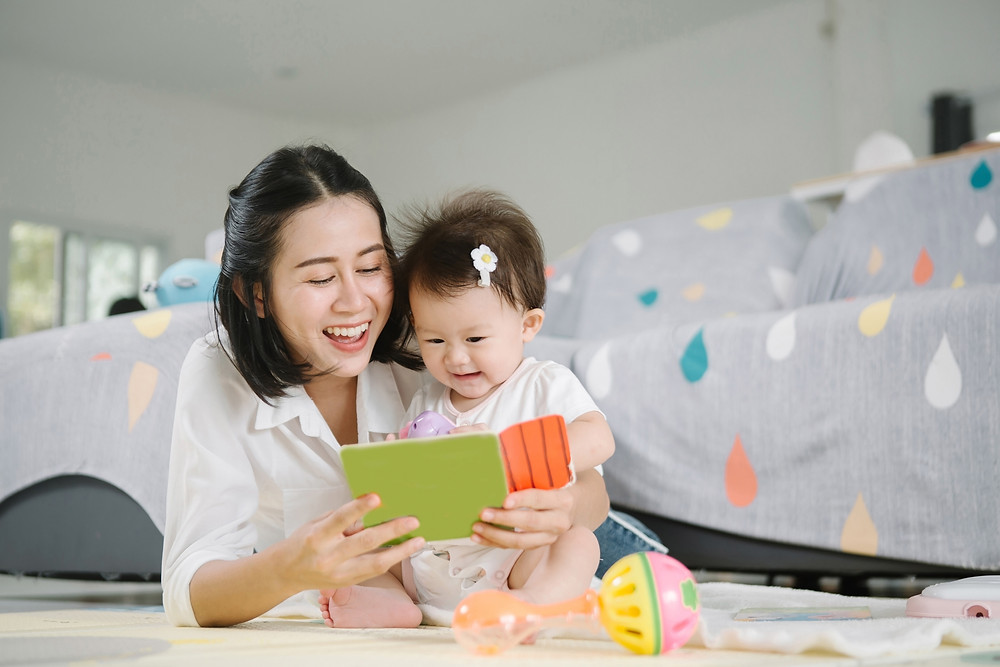 mother and child having fun while reading a book together