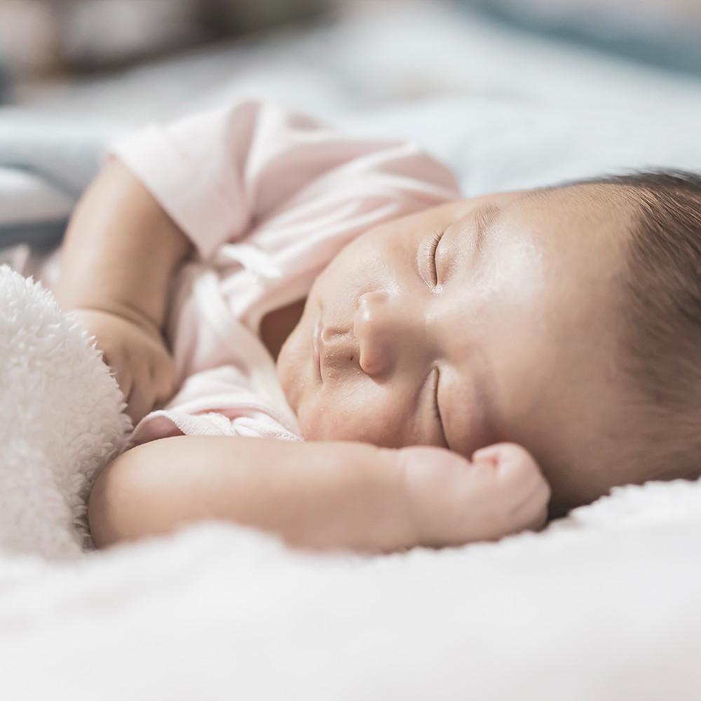 baby sleeping comfortably on bed