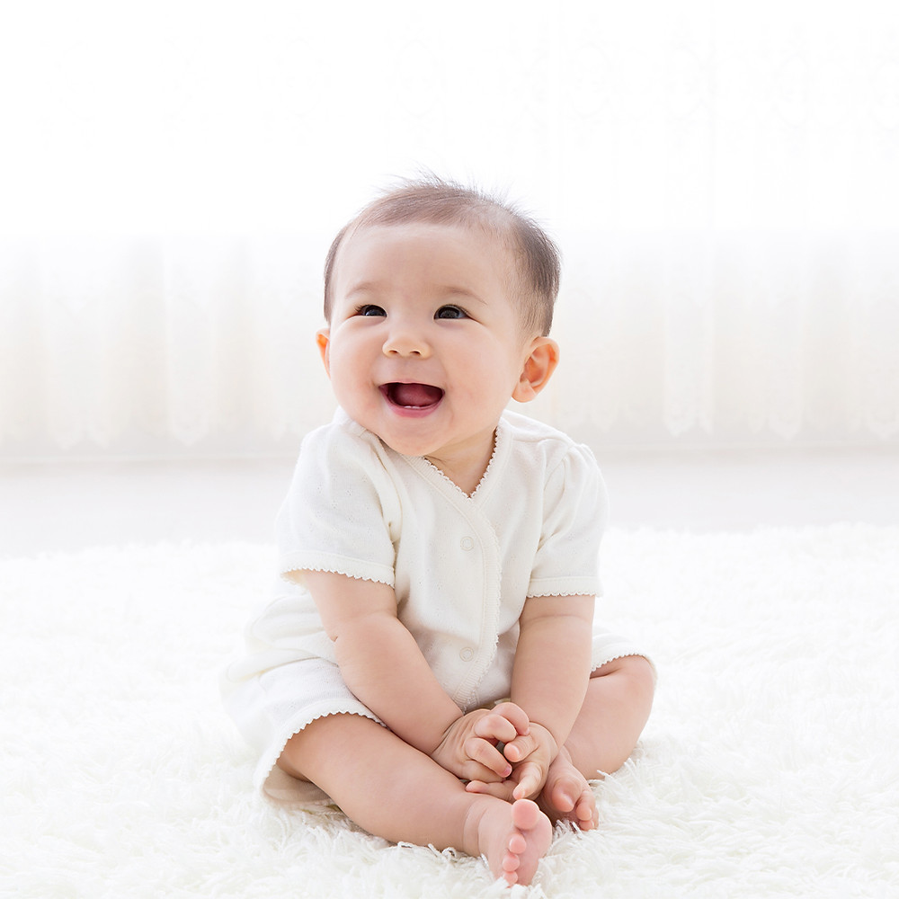 baby happily smiling while sitting on floor