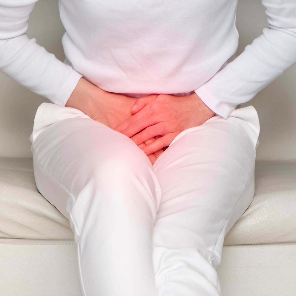 woman holding her stomach due to urinary incontinence