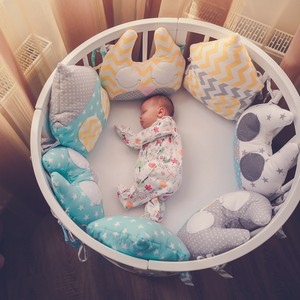baby sleeping in a round crib