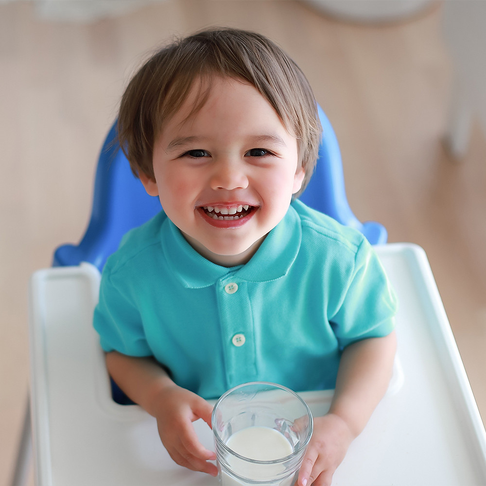 toddler looking up from chair after drinking milk