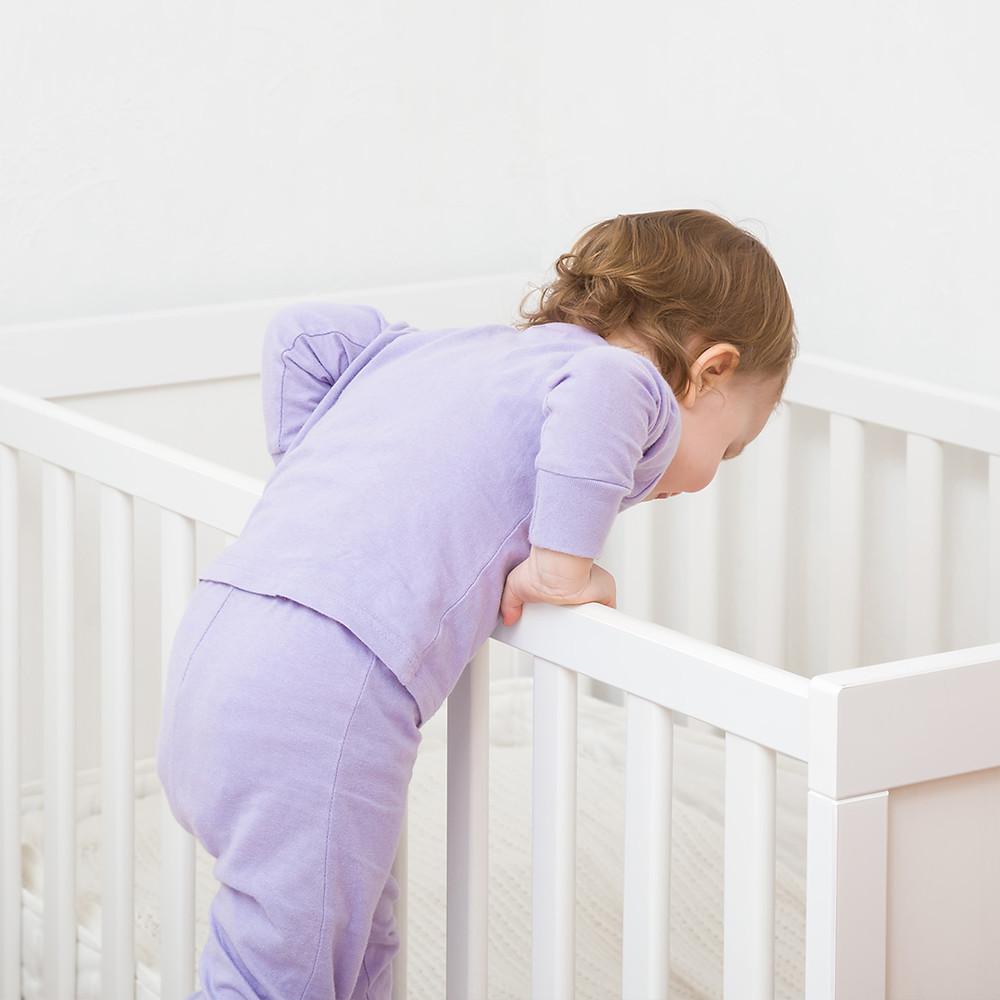 toddler climbing out of crib