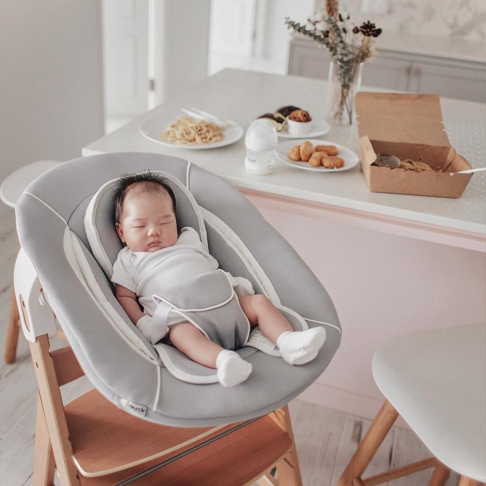 newborn baby sleeping on Hauck's Alpha Bouncer in the kitchen