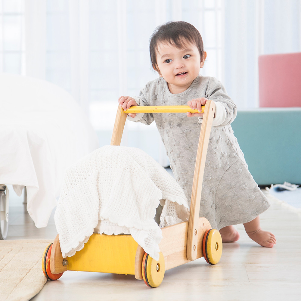 cute baby smile and happy face crawling and try to walk on wood floor at white bedroom