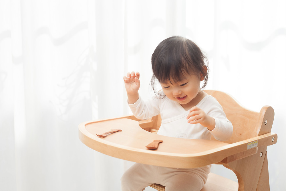 baby girl having fun while sitting on her high chair
