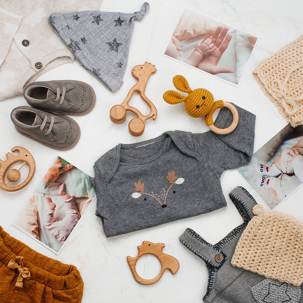 laid out baby clothes and toys