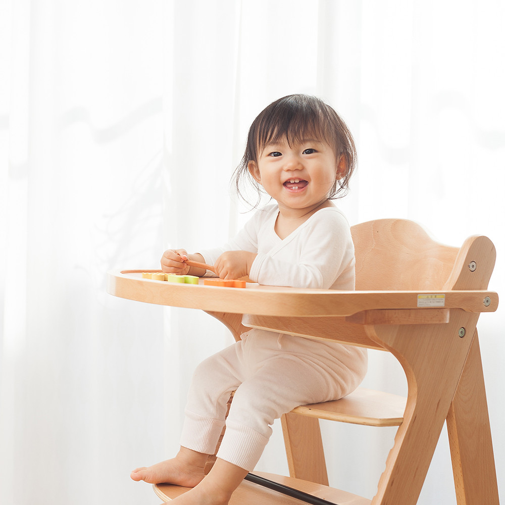 baby girl happy sitting on her high chair