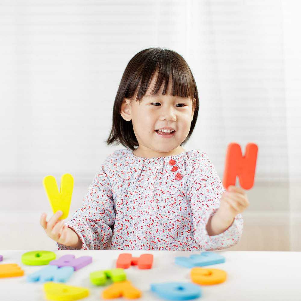 toddler girl having fun while learning letters
