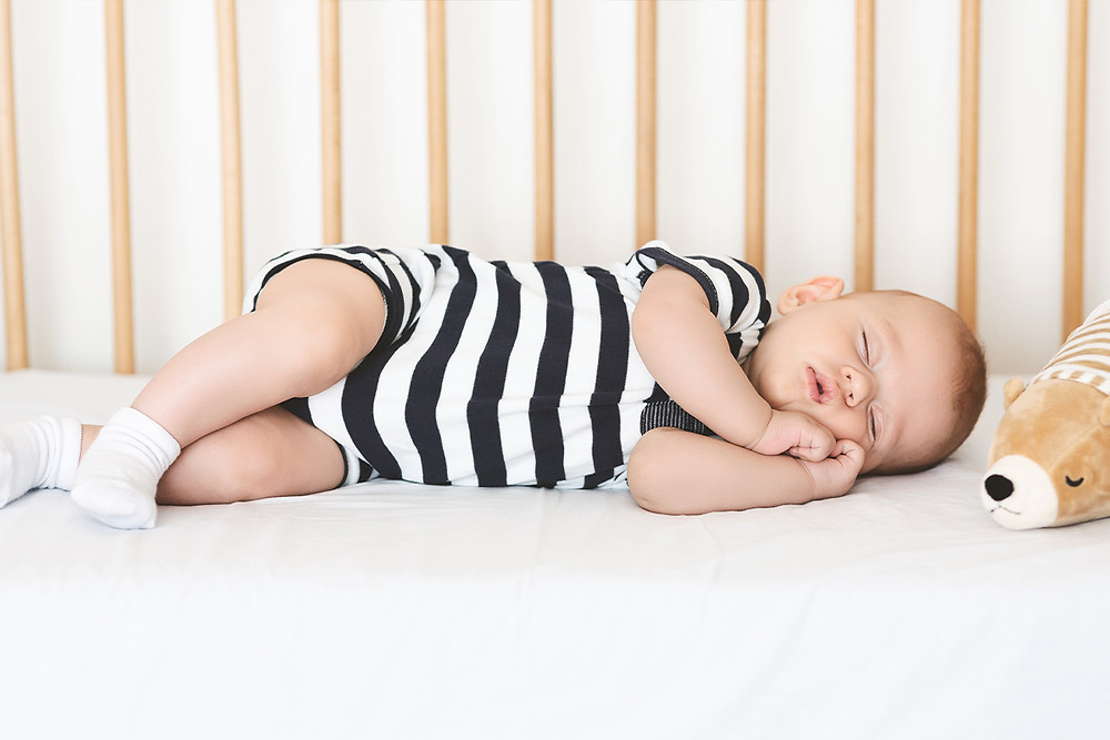 Adorable newborn boy napping on his side in crib
