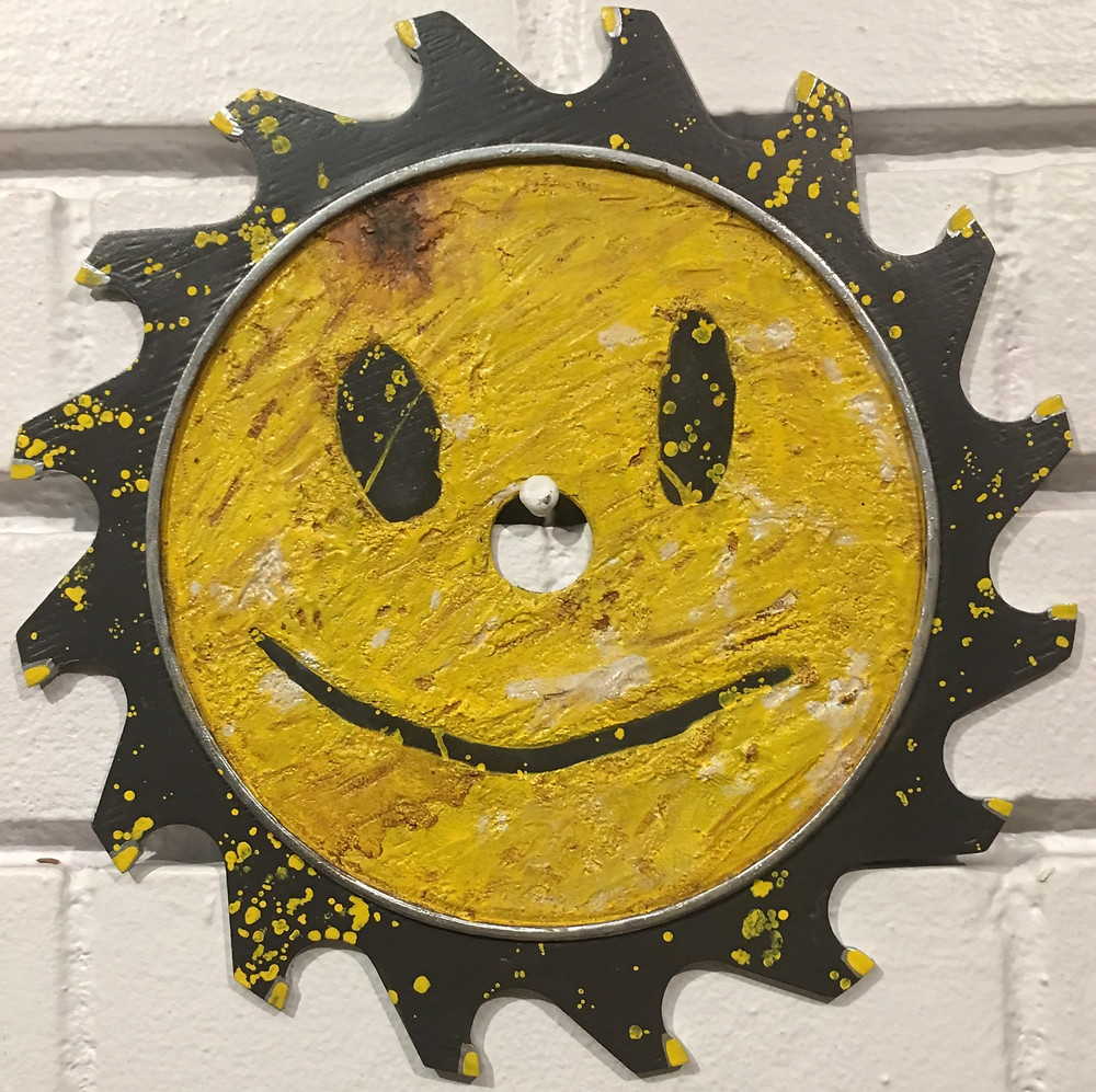 A yellow saw blade with a smily face from far cry hanging on a wall