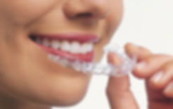 Close up of a person holding a clear retainer near their teeth