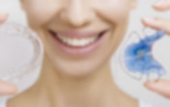 Smiling woman holding a a clear Essix retainer and a metal Hawley retainer