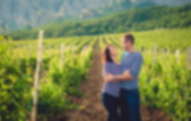 Couple standing in a field look at each other.