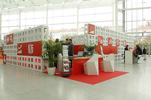 Mehrfach wiederverwendete Messelandschaft / Gemeinschaftsstand aus dem Cube-System mit Loungebereich, Infoständen und kleiner Präsentationsbühne