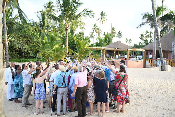 Destination Wedding guests toast the bride and groom on the beach in the Dominican Republic