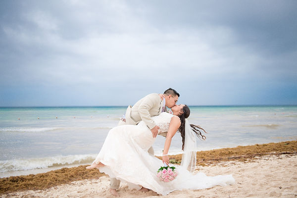 Bride and groom dipping for kiss on the beach at their Mexico destination wedding at Ocean Rivera Paradise in Cancun.