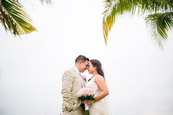 Tropical palm trees frame the bride and groom at their Mexico Destination Wedding