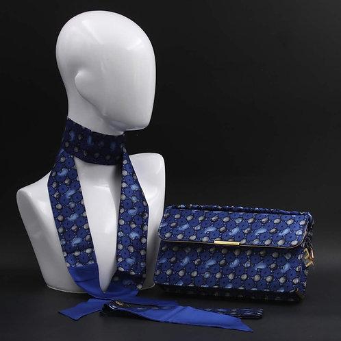 Clutch bag in seta blu stampata con disegni geometrici, nelle tonalità del blu.