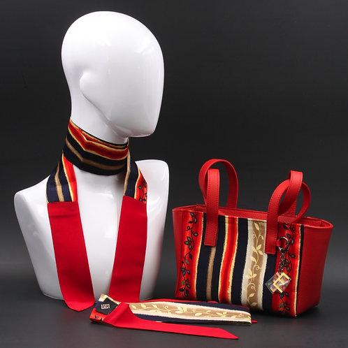 Borsa a spalla in vera pelle rossae inserti in seta con stampa floreale, con tonalità rosse e blu.  Manici rossi