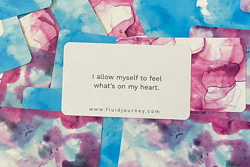 """Text on a card that reads """"I allow myself to feel what's on my heart."""" This card sits face-up on top of other cards."""