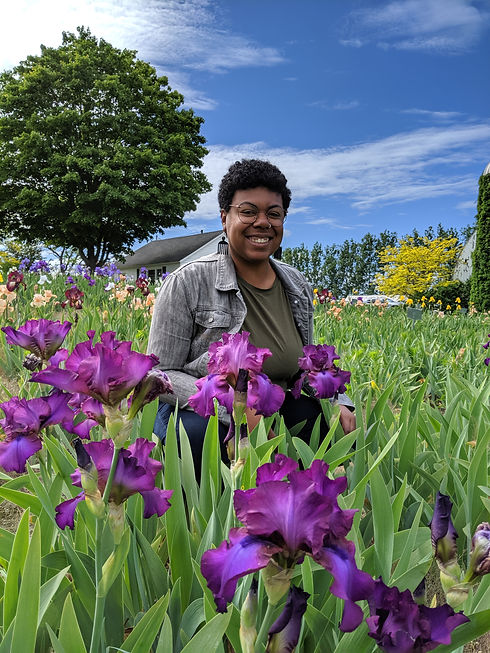 AmariYah, who is a brown skin Black person with a short Afro, smiles wearing a gray jean jacket, a green shirt, Afro pick earrings, and round glasses in a field of purple iris flowers. Photo credit Matthew Klein