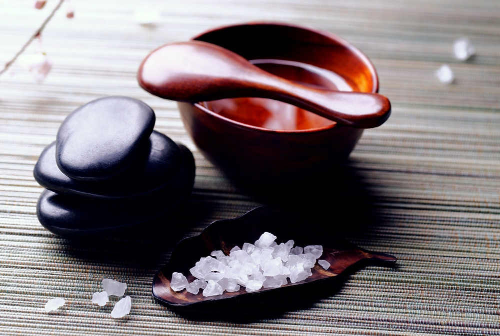 Salt crystals with wooden spoon, bowl and polished stones