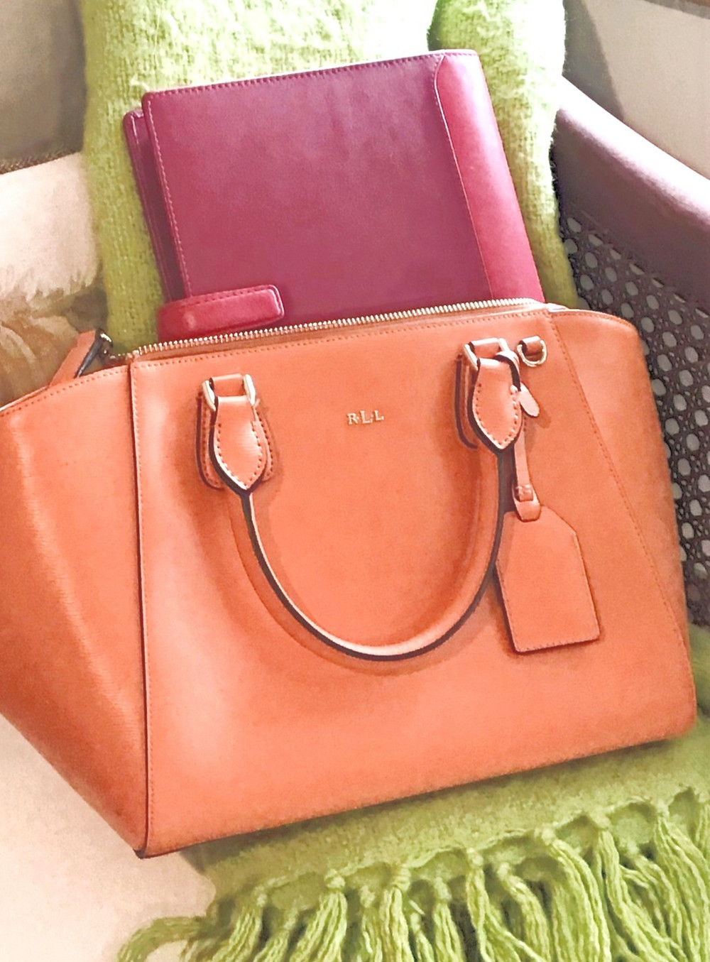 Orange bag on a lime green throw with pink diary