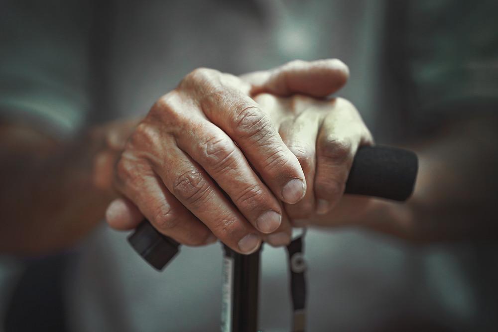 hands of elderly man holding walking stick