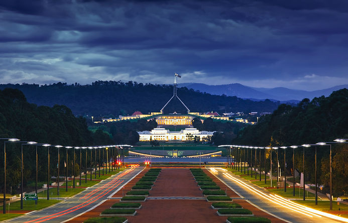 Image of Parliament House at Canberra at dusk. The sky has dark clouds.
