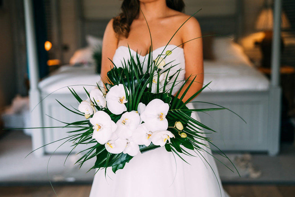 white orchid and tropical foliage bouquet