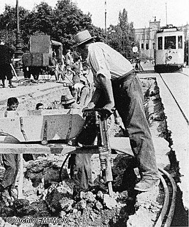 Vorbei an einem Bautrupp mit Kompressor VIII fährt ein D-Tw auf der Maximiliansbrücke 1937 tram München