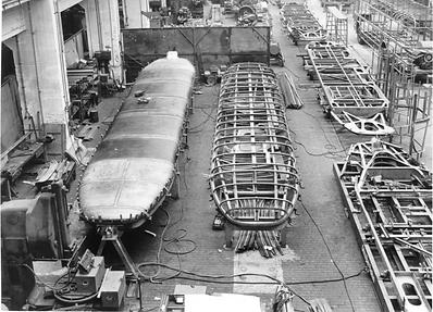 Der Bau der neuen Großraumwagen wird bei Rathgeber im Taktverfahren durchgeführt. Dieser Blick in die Montagehalle der Moosacher Waggonfabrik zeigt am 28.9.53 zwei Wagendächer in unterschiedlichem Fertigungsstand. Rechts davon entstehen die Grundrahmen der Wagenkästen münchen tram trambahn rathgeber moosach