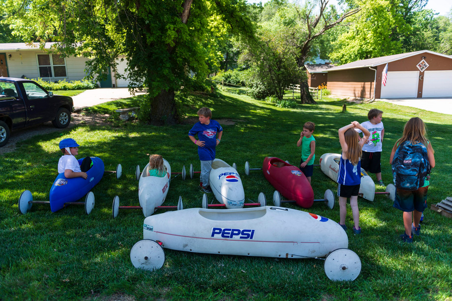 Children check out the soapbox derby cars before rides get started during the Independence Day celebration at Triangle Park in Randolph, Kansas on Saturday.