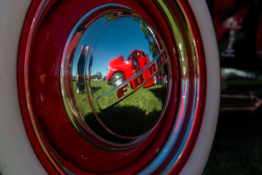 A 1935 Ford five window coupe is reflected in the hubcap of another 1935 Ford at the MATC car show on Saturday in Manhattan, Kansas. The Manhattan Area Technical College hosts it's third annual car show and fall celebration to bring attention to it's automotive technology collision programs. Upwards of 50 cars were on display.