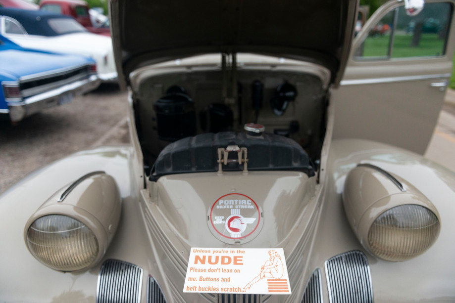A sign sits on a 1939 Pontiac Silver Streak during the Yard Art Car Show at City Park on Saturday in Manhattan, Kansas.