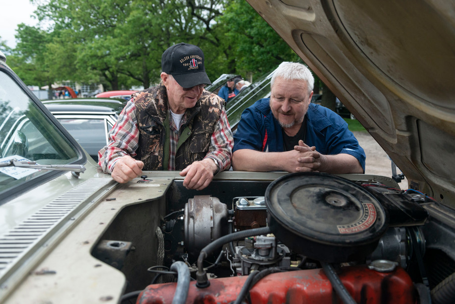 Richard Stahl of Dwight and Andy Rodgers of Junction City talk about the shift points on the 1973 International Scout during the Yard Art Car Show at City Park on Saturday in Manhattan, Kansas.