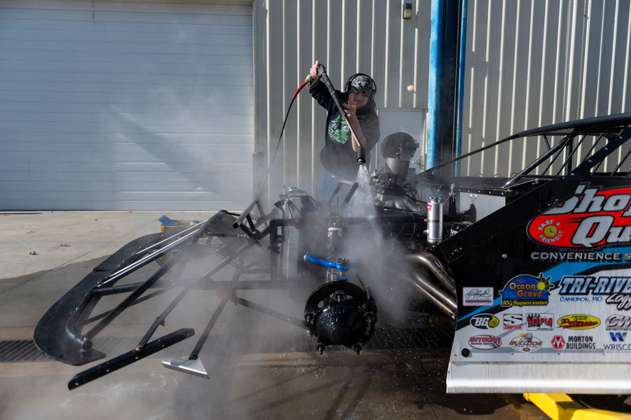 Crew member Corey Richman uses a power washer to clean a racecar outside of the team shop in Manhattan on Wednesday. Chase Junghans drives the car in the World of Outlaws Craftsman Late Model Series. Finishing 6th in the points in 2018 with one win at Eriez Speedway in Erie, PA.
