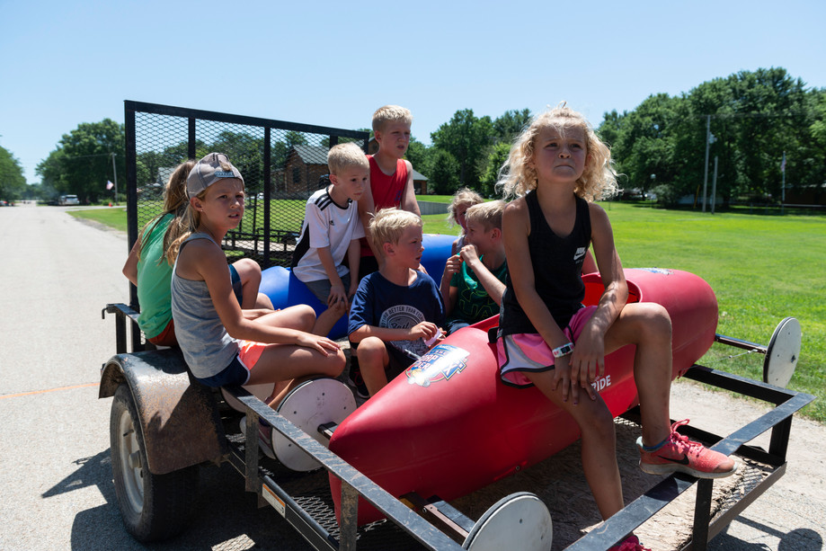 Children climb in the back of a trailer with soapbox derby cars to go back to the top of the hill for the next run during the Independence Day celebration at Triangle Park in Randolph, Kansas on Saturday.