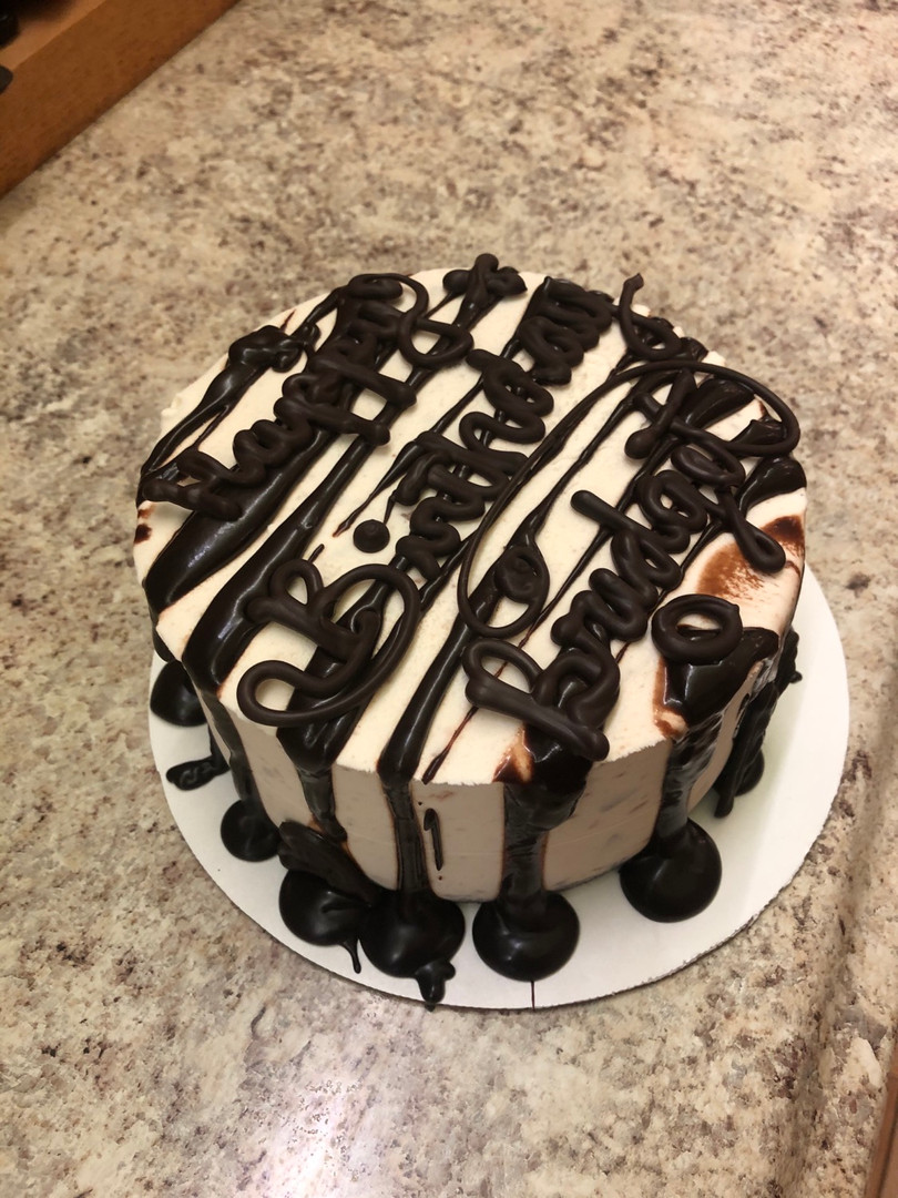 Oreo and vanilla ice cream cake with thick fudge drizzled across the top and sides