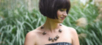 Brunette woman in front of tall grass wearing necklace