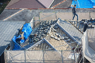 people-working-to-tile-a-roof-damaged-by