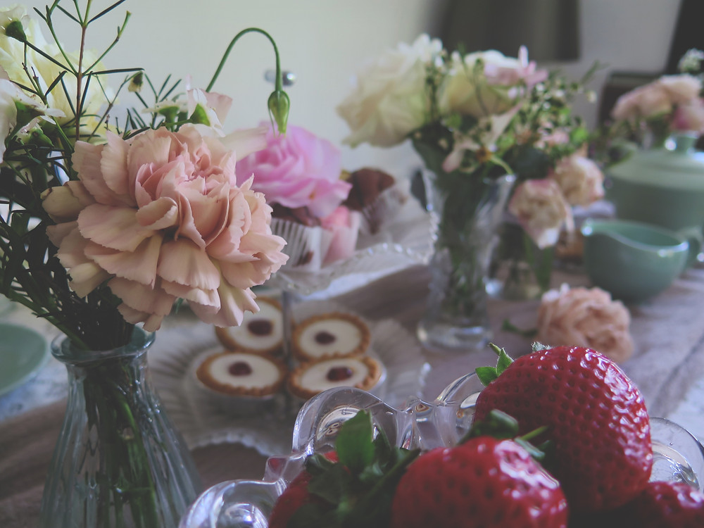 A floral filled table setting for afternoon tea