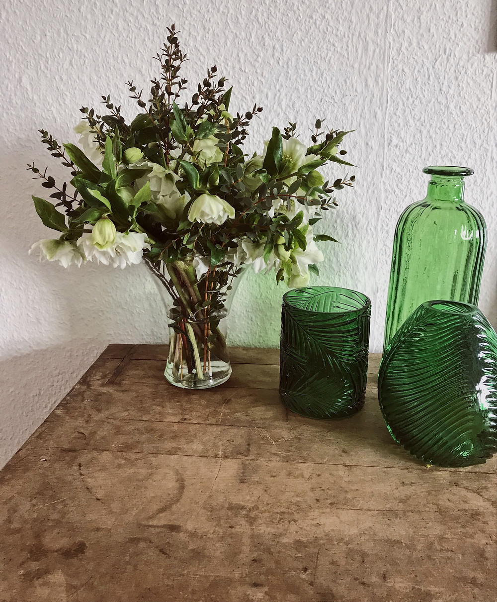 Natural cream and green flowers and foliage vase arrangement displayed with green bottles and containers