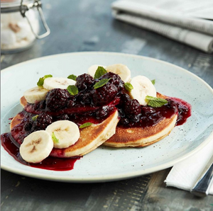 Two thick pancakes drizzled with fresh berry compote and sliced bananas