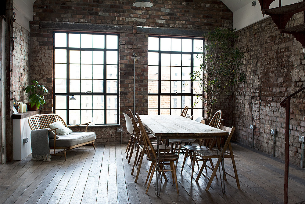 Rustic and industrial interiors of The Forge in Bristol showing bare brick walls and wooden floors with a central table and large windows