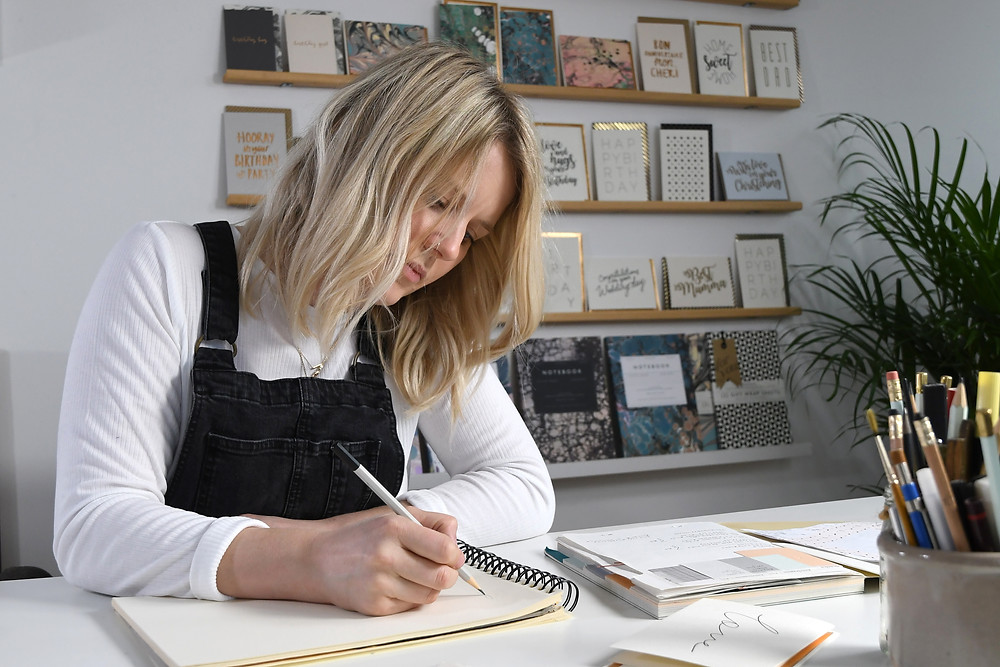 Katie Leamon a luxury card and stationery brand sits in her London studio hand creating beautiful paper products