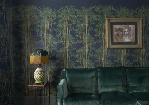 House of Hackney wallpaper styles a living room with a green velvet sofa and table lamp