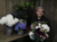 Owner of wild about flowers florist Angela stands infront of a flower stand holding a bouquet