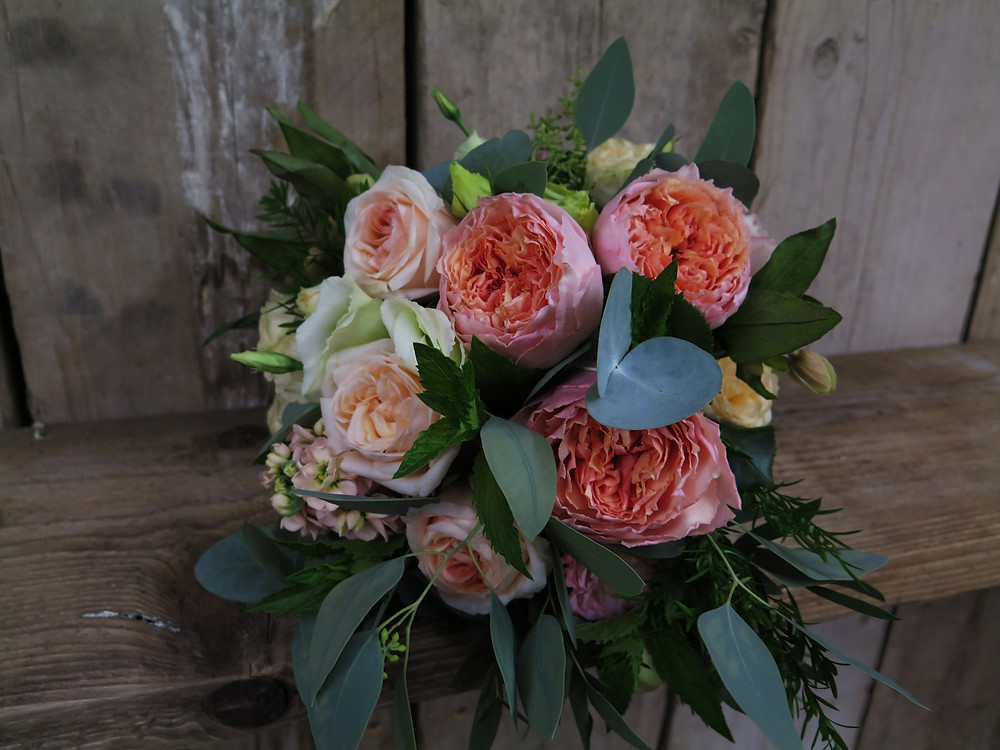 A beautiful bridal bouquet using coral and peach tones compliments the Living Coral colour palette  for 2019
